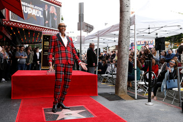 Television personality and drag queen RuPaul poses on his star after it was unveiled on the Hollywood Walk of Fame in Los Angeles