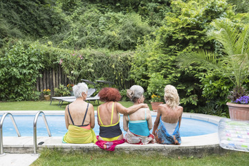 Senior women friends sitting in swimming pool