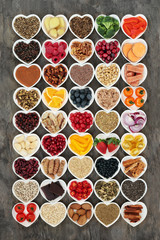 Healthy food concept with fruit, vegetables, fish, seeds, nuts, grains, cereals, herbs and spices also used in herbal medicine to promote heart health. Super foods high in omega 3 &  antioxidants.