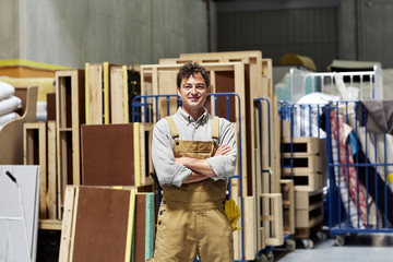 Confident Male Worker Standing In Sofa Workshop