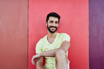 Handsome bearded man smiling at camera over colorful background.