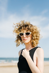 Pretty young woman with curls and sunglasses posing on  beach