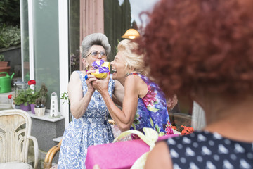 Playful senior women exchanging gifts during birthday party