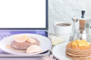 Workplace. Laptop with blank screen on table with breakfast: pancakes and coffee. Front view. Copy space