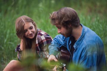 Man romantically serenades his girlfriend around the campfire