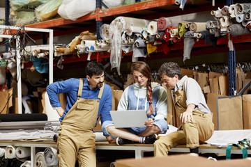 Workers Using Laptop At Warehouse In Sofa Workshop