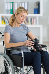 female photographer in wheelchair holding a professional camera