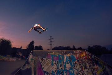 Male skater jumping in midair on ramp in skate park