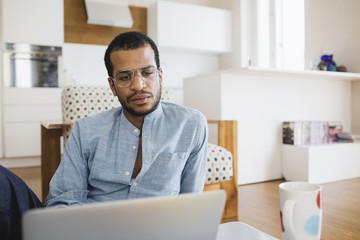 Smiling man at home using his laptop