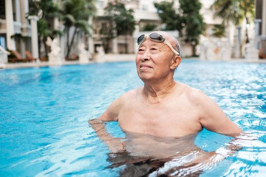 Senior Asian Man Standing in the Swimming Pool