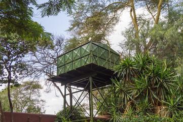 One green water storage tanks on stilts in the savannah of Amboseli Park in Kenya