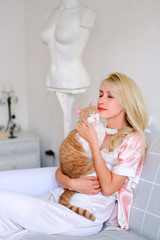 Portrait of a blond female model with her cat at home