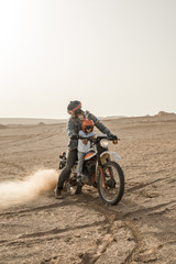 father and son on a motorcycle in iranian desert