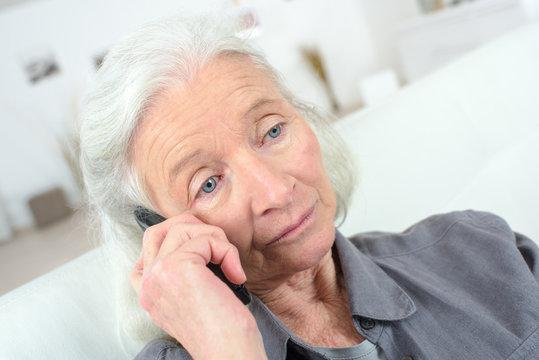 upset senior woman on the phone