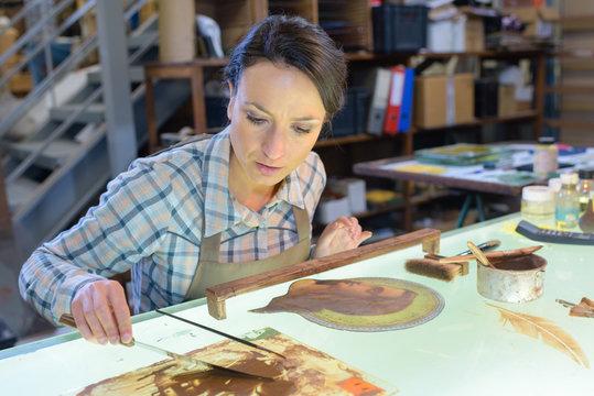 Female artist restoring picture