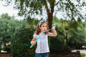 Cute young girl blowing bubbles