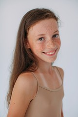 Lovely girl with freckles and happy smile posing at studio and looking at camera