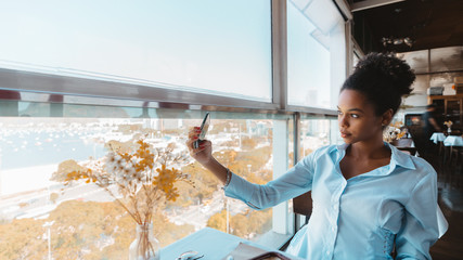 Exquisite Afro girl in a teal shirt with curly hair is taking a selfie using her smartphone while sitting inside of a luxury restaurant on a top-floor next to the window with a cityscape outside