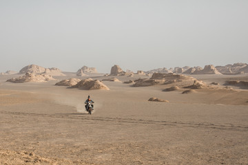 father and son on a motorcycle riding through iranian desert landscape