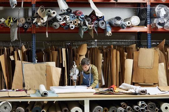 Male Worker Using Fabric Cutter In Sofa Workshop