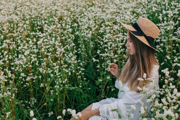 Side view portrait of pretty young female in straw hat and white outfit enjoying free time at nature