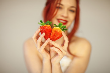 beautiful woman holding some strawberries in her hands, sensual studio shot can be used as background