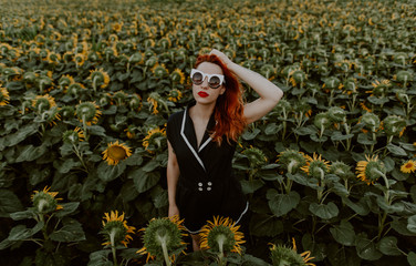 ginger woman with cool sunglasses in a field of sunflowers
