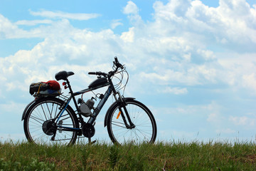 Motorized bicycle on green grass against blue sky background Wall mural
