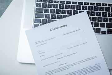 German Arbeitsvertrag or Employment Contract lying on an open laptop keyboard wth a pen waiting to be completed with a job offer, salary and conditions in an overhead view