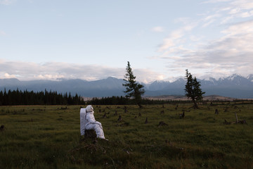 Cosmonaut sitting in field looking up