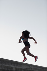 Young athlete running upward on the bleachers against clear sky