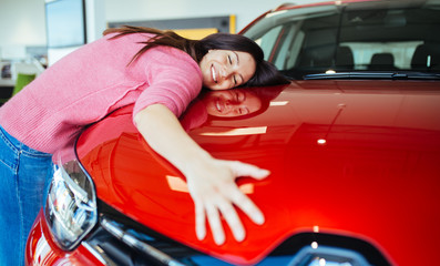 Happy beautiful young woman buying a new car at the car showroom.