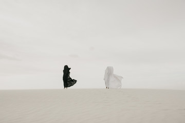 Black vs White contrast concept of two humans draped in fabric in the desert