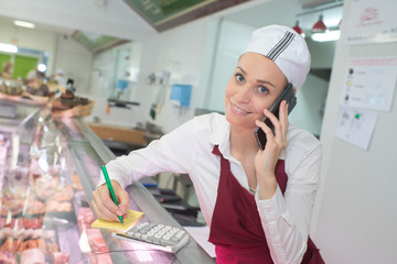 Woman in butchers taking phone order