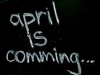 april is comming text on blackboard isolated