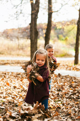 Autumn: Little Girl Carrying Handfuls Of Leaves