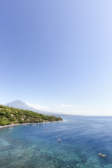 View of Amed village Agung volcano shallow reef and jukung boats floating in the bay of Jemeluk in Bali
