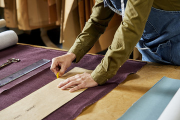 Worker Using Cardboard Paper And Chalk To Mark On Fabric
