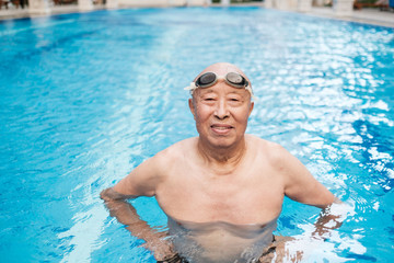 Senior Asian Man Standing in the Swimming Pool