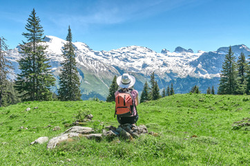 Swiss Alps. A woman in a white hat is sitting on a green meadow, admiring the mountain scenery. Engelberg Resort