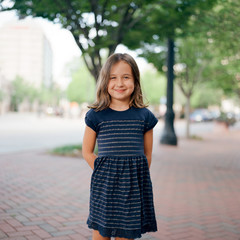 Cute young girl in a dress standing on on a street