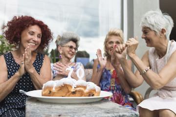 Playful happy seniors women having fun at birthday party