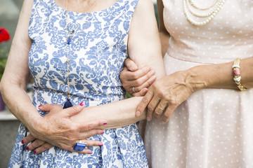 Unrecognisable senior ladies hand in hand