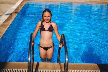 Little girl exiting pool and having hard time looking