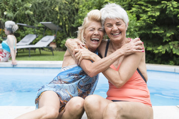 Playful senior women friends portrait at swimming pool