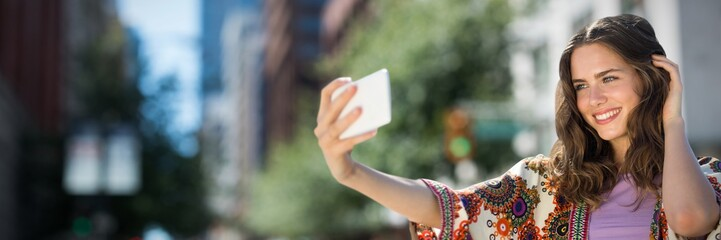 Composite image of smiling girl taking a selfie