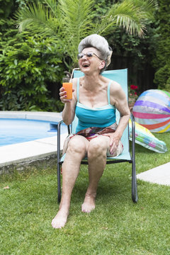 Senior woman in swimsuit enjoying drink near swimming pool