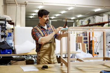 Worker Fixing Clamp On Wooden Frame While Making Table