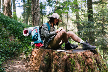 Young hiker man writing in a notebook sitting on an old big trunk.