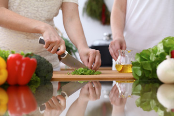 Closeup of human hands cooking in kitchen. Mother and daughter or two female cutting green salad or herbs. Healthy meal, vegetarian food and lifestyle concepts